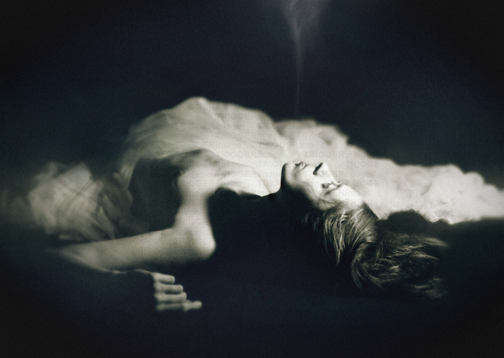 A young woman laying on the ground, half naked & covered in a white veil.