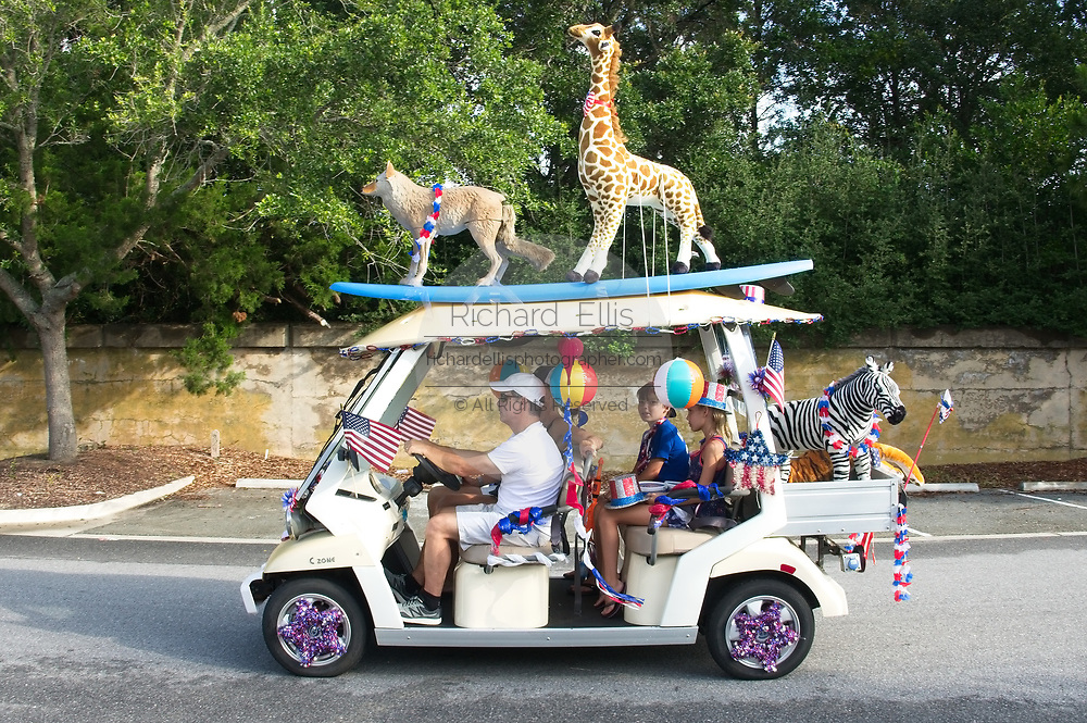 A family rides along in a golf cart decorated with stuffed animals during the annual Sullivan's Island Independence Day parade July 4, 2017 in Sullivan's Island, South Carolina. The tiny affluent sea island hosts a bicycle and golf cart parade through the historic village.