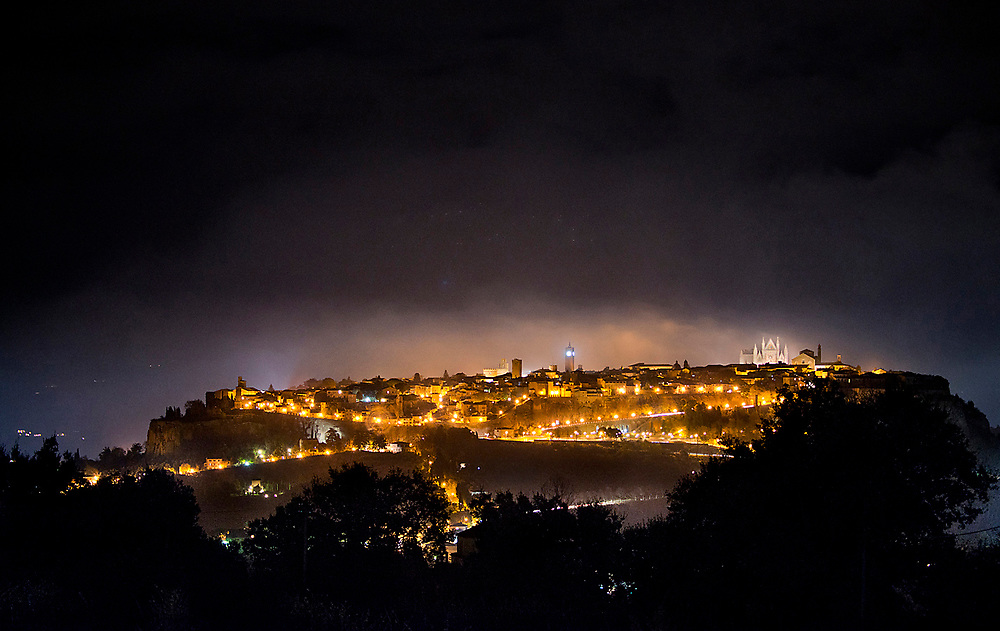 Night fog rolls in over historic Orvieto, Italy