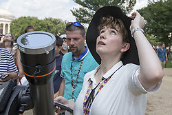August 21, 2017 - Washington, District of Columbia, U.S. - A National Air and Space Museum employee adjusts a telescope for museum visitors during the 2017 Solar Eclipse. (Credit Image: © Alex Edelman via ZUMA Wire)