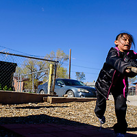 Keisha Henry takes a swing while playing a game of stickball with Josiah James at their home in Gallup Tuesday.