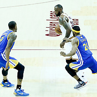 07 June 2017: Cleveland Cavaliers forward LeBron James (23) drives past Golden State Warriors guard Ian Clark (21) and Golden State Warriors forward Andre Iguodala (9) during the Golden State Warriors 118-113 victory over the Cleveland Cavaliers, in game 3 of the 2017 NBA Finals, at  the Quicken Loans Arena, Cleveland, Ohio, USA.