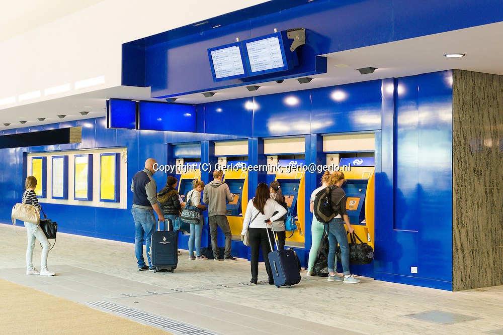 Nederland, Breda, 20140912.<br /> Reizigers in de nieuwe voetgangerspassage. Bij de kaartautomaten. De noordkant van het station in gebruik is genomen. Het compleet nieuwe station van Breda brengt reizen, wonen, werken en winkelen op een moderne en comfortabele manier samen. Door een nieuw busperron voor twintig bussen, parkeerruimte voor 4.400 fietsen en meer dan 700 auto&rsquo;s, woningen, kantoren en winkels in het station zelf. Opgezet op een ruime en toegankelijke manier, met een brede voetgangerspassage, overzichtelijke pleinen en brede wegen. De zes sporen en drie perrons op station Breda bieden ruimte aan 16 treinen per uur.<br /> <br /> Netherlands, Breda, 20140912.<br /> The completely new railway station of Breda will travel, live, work and shop in a modern and comfortable way together. A new bus platform for twenty buses, parking for 4,400 bikes and over 700 cars, homes, offices and shops in the station itself. Mounted on a spacious and accessible way, with a wide pedestrian passage, clear squares and wide roads. The six tracks and three platforms at Breda station for up to 16 trains per hour.