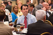 Wisconsin Governor and potential Republican presidential candidate Scott Walker sits with supporters during a GOP lunch event March 20, 2015 in Charleston, South Carolina.