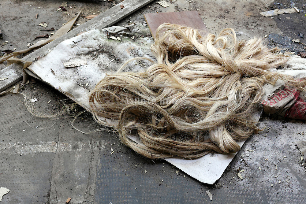 garbage with big strand of what looks like curly blond hair