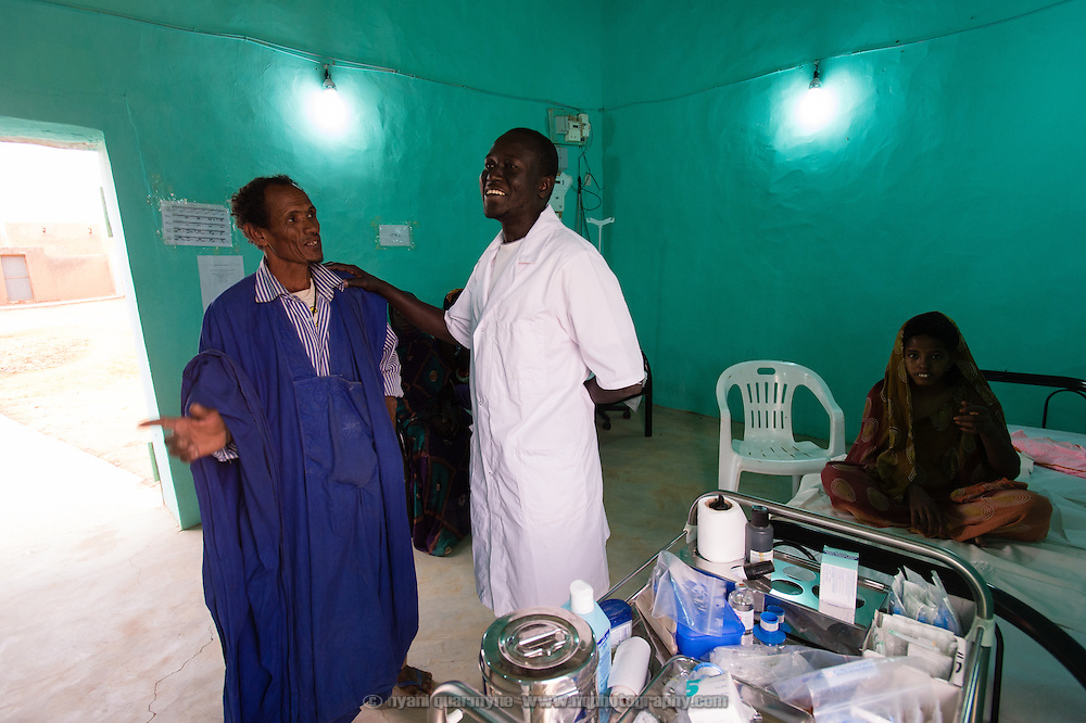 Médecins Sans Frontières (MSF) nurse, Ibrahima Ba, with the relative of a patient at the MSF operating theatre in Bassikounou, Mauritania on 2 March 2013.