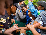 03 SEPTEMBER 2016 - BANGKOK, THAILAND: Pom Mahakan residents tussle with Bangkok code enforcement officials at a back entrance to the Pom Mahakan community. Hundreds of people from the Pom Mahakan community and other communities in Bangkok barricaded themselves in the Pom Mahakan Fort to prevent Bangkok officials from tearing down the homes in the community Saturday. The city had issued eviction notices and said they would reclaim the land in the historic fort from the community. People prevented the city workers from getting into the fort. After negotiations with community leaders, Bangkok officials were allowed to tear down 12 homes that had either been abandoned or whose owners had agreed to move. The remaining 44 families who live in the fort have vowed to stay.      PHOTO BY JACK KURTZ