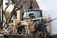 A house at 363 Wayne Drive is damaged, and the house that used to be behind this backhoe was destroyed in what appears to be a gas-line explosion in Fairborn, Saturday, November 12, 2011.