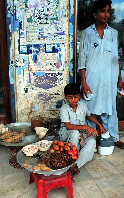 Pakistan, La Hore,  1995.Kinderarbeid. Jochie helpt met verkopen van voedsel in de straten van La Hore..Foto (c) Michiel Wijnbergh/Hollandse Hoogte