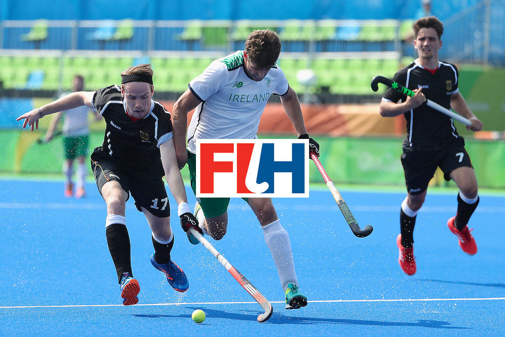 RIO DE JANEIRO, BRAZIL - AUGUST 09:  Christopher Ruhr #17 of Germany and John Jermyn #11 of Ireland battle for the ball during the hockey game on Day 4 of the Rio 2016 Olympic Games at the Olympic Hockey Centre on August 9, 2016 in Rio de Janeiro, Brazil.  (Photo by Christian Petersen/Getty Images)
