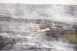 © Licensed to London News Pictures . 04/07/2018 . Bolton , UK . Free to use aerial photograph provided by the Woodland Trust showing a helicopter dowsing the scarred landscape at Winter Hill , as fire-fighters continue to work to control the spread of the blaze . The Woodland Trust estimates it has lost a fifth of the area it manages around Winter Hill , damaging precious moors and upland grassland , endangering the surrounding woods and wildlife and threatening people's homes . Photo credit: Joel Goodman/LNP