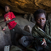 Nader takes a rest in one of the mountains caves near the front lines of Meitan. A family has moved there in order to avoid the regular bombings taking place in their area.