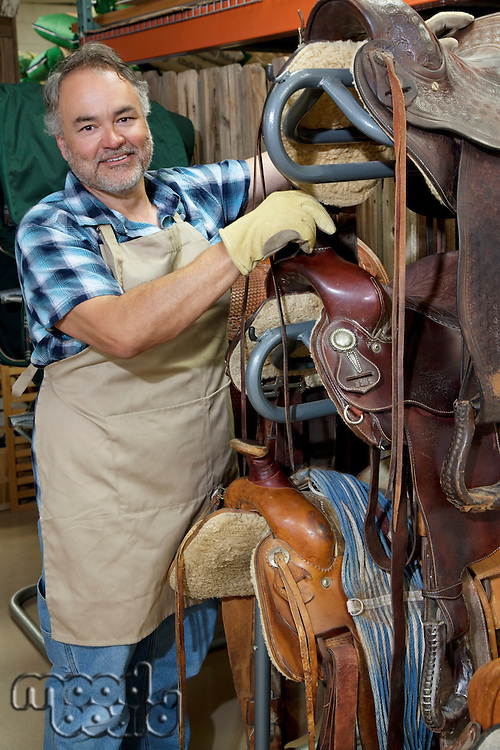 Portrait of a happy mature salesperson standing by horse riding tack in feed store