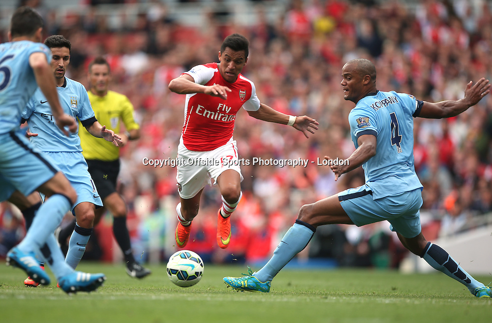 13 September 2014 , Premier League ,  Football Arsenal v Manchester City - Alexis Sanchez of Arsenal skips over the tackle of City captain Vincent Kompany.<br /> Photo: Mark Leech