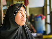 29 OCTOBER 2012 - MAYO, PATTANI, THAILAND:  NURIAH JETEH looks out from her house at the Bukit Kong home in Mayo, Pattani. The home opened 27 years ago as a ponoh school, or traditional Islamic school, in the Mayo district of Pattani. Shortly after it opened, people asked the headmaster to look after individuals with mental illness. The headmaster took them in and soon the school was a home for the mentally ill. Thailand has limited mental health facilities and most are in Bangkok, more than 1,100 kilometers (650 miles) away. The founder died suddenly in 2006 and now his widow, Nuriah Jeteh, struggles to keep the home open. Facilities are crude by western standards but the people who live here have nowhere else to go. Some were brought here by family, others dropped off by the military or police. The home relies on donations and gets no official government support, although soldiers occasionally drop off food. Now there are only six patients, three of whom are kept chained in their rooms. Jeteh says she relies on traditional Muslim prayers, holy water and herbal medicines to treat the residents. Western style drugs are not available and they don't have a medic on staff.    PHOTO BY JACK KURTZ