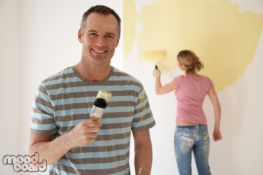 Smiling man holding paintbrush while woman paints wall with roller