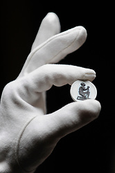 "© Licensed to London News Pictures. 23/03/2017. London, UK.   A technician shows a Wedgwood anti-slavery medallion, circa 1790, bearing the incription ""AM I NOT MAN AND A BROTHER?"" (Est. GBP800-1,200).  Preview at Sotheby's New Bond Street of property from two great Scottish families, the Forbeses of Pitsligo and the Marquesses of Lothian, which will be auctioned in London on 28 March.   Photo credit : Stephen Chung/LNP"