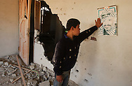 Gaza, Palestine.  Odai Alquenwa, 14, holds a poster of Yasser Arafat in the destroyed house of his uncle Akram Ghoniem.  At the end of  the 22 day military campaign by Israel inside Gaza, known as Operation Cast Lead. (PHOTO: MIGUEL JUAREZ LUGO).