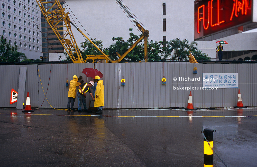 "On the eve of transfer of law in Hong Kong from the UK to China, construction workers in Central Hong Kong carry on their tasks during a monsoonal rain shower on the last day of British rule. Some are dressed in yellow waterproof coats and hard hats, we see a British-style sign warning drivers of Men at Work resembling a man holding an umbrella. Lastly, on the right another man on a wall, also holding an brolley. In the foreground a car park sign states that the space is full in red letters and a local authority sign saying ""Working for a better environment"" is written in Chinese and English lettering. The transfer of sovereignty of Hong Kong from the United Kingdom to China, referred to as ""The Handover"" occurred at midnight on June 30, 1997, signifying the end of British rule, and the transfer of legal and financial authority back to China."