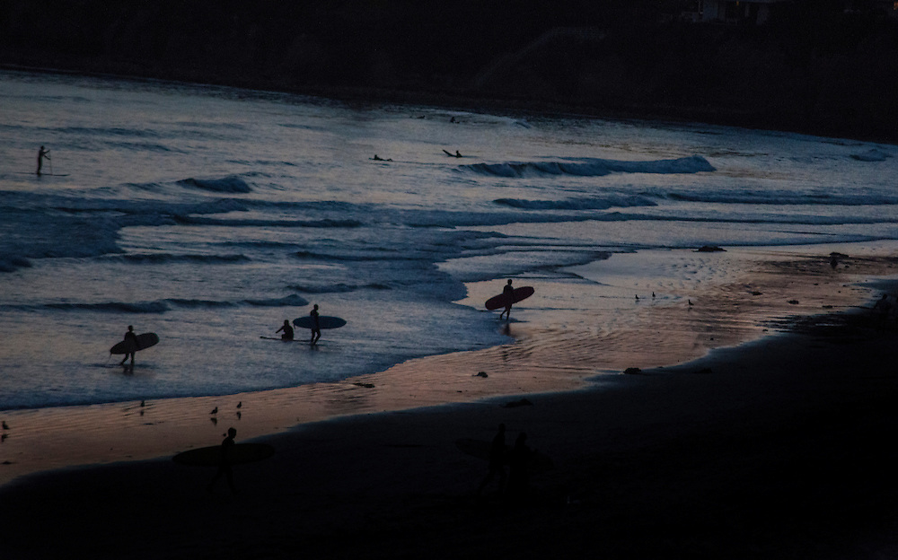 La Jolla surfers making their way from the ocean after sundown.