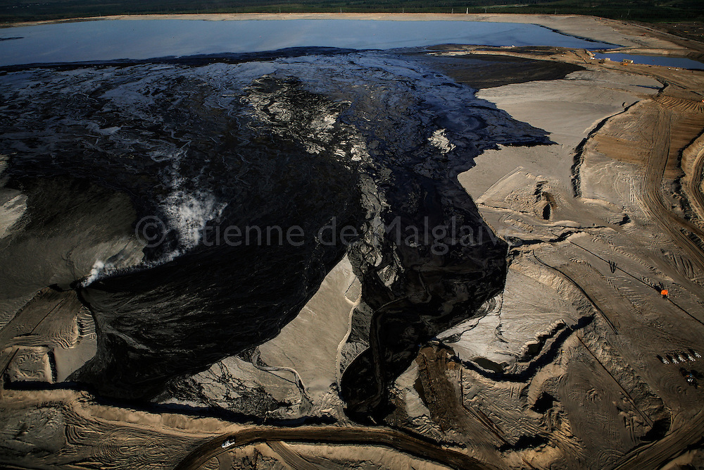 Tailing pond seen from the air.<br /> During the process of separating bitumen from the tar sands, large amounts of water are mixed in with the sand, and once the oil has been removed, the leftover mixture of water, sand, clay and residual bitumen - known as tailings - has to be stored outdoor in a stable location so that the solution can settle and separate.  June 2008.