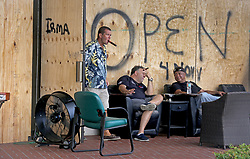 Todd Tarczynski walks outside to join Harris Safra, the owner of Xavier's Cigar Lounge in Hallandale Beach and William Brown. The men were enjoying cigars before Hurricane Irma.  (Mike Stocker/Sun Sentinel/TNS/Sipa USA)<br />SOUTH FLORIDA OUT; NO MAGS; NO SALES; NO INTERNET; NO TV