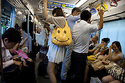 TOKYO, JAPAN, 22 AUGUST - A woman hang the handle arms up in a crowded train and let appears that very big smiley face printed on her yellow bag - August 2012