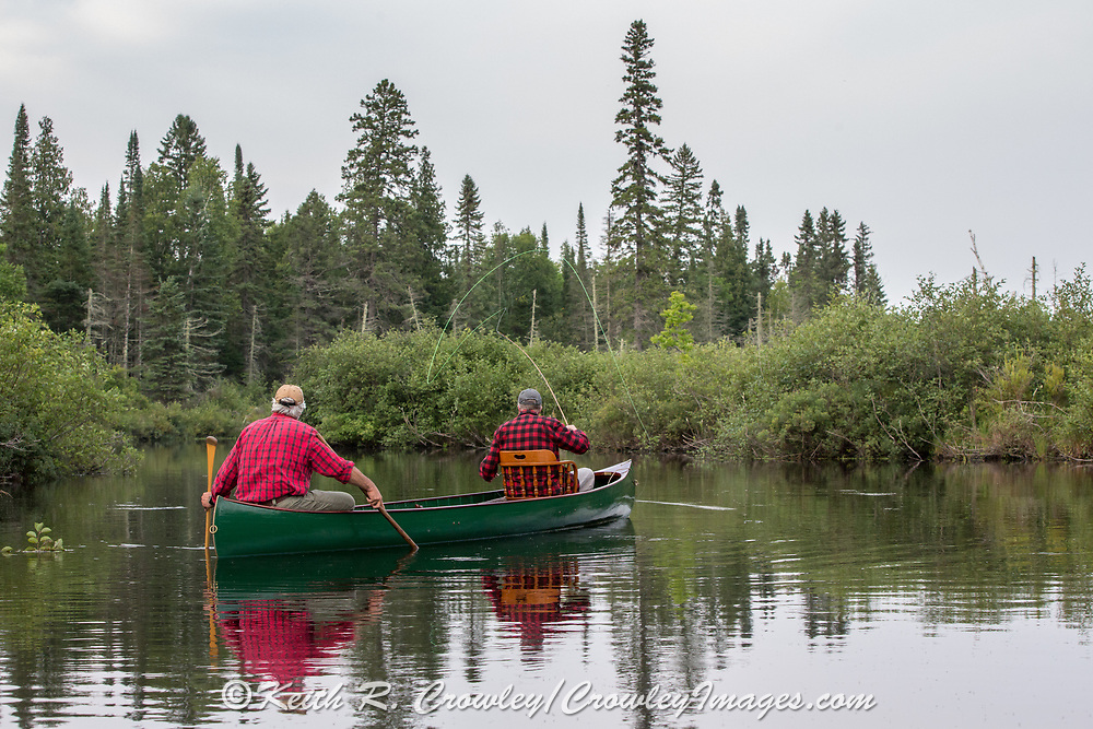 Brule River fishing guide Damian Wilmot (left) fishes the upper Brule with angler Matson Holbrook in a 1895 Joe Lucius guide canoe Wilmot meticulously restored over the course of two years.