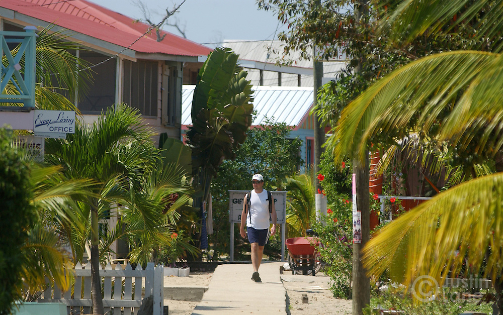A man is seen strolling down the small sidewalk that runs through the small town of Placencia, Belize, a beach town in the southern part of the country.<br />JUSTIN LANE FOR THE NEW YORK TIMES