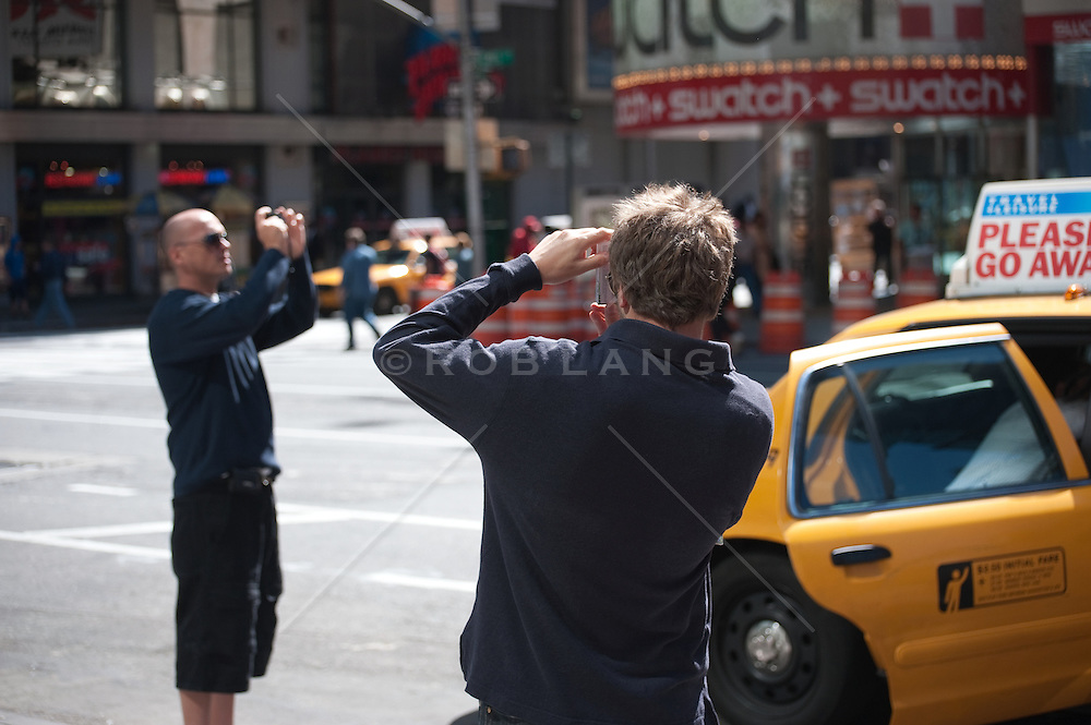 Two men taking photographs in Times Square, NY