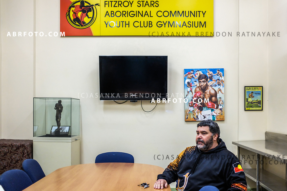 Troy Austin sits in a meeting room with posters and framed pictures of Aboriginal sporting greats such as boxer Lionel Rose at the Aboriginal Youth Sport and Recreation centre in Melbourne, Australia, August 30, 2017. Asanka Brendon Ratnayake for the New York Times