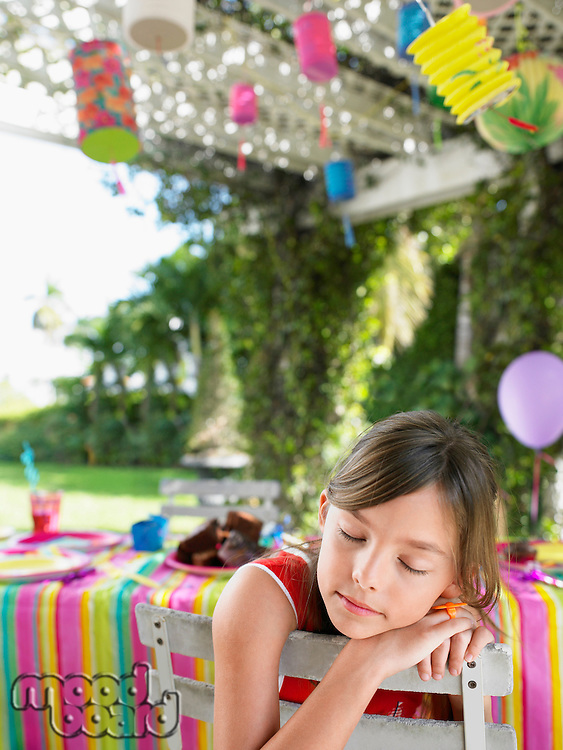 Young girl (7-9) sleeping on patio after birthday party close-up