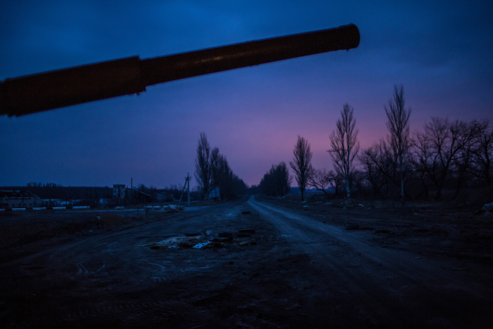 PERVOMAISKE, UKRAINE - MARCH 19, 2015: The barrel of a tank hovers over the road leading to the embattled town of Pisky in Pervomaiske, Ukraine. CREDIT: Brendan Hoffman for The New York Times