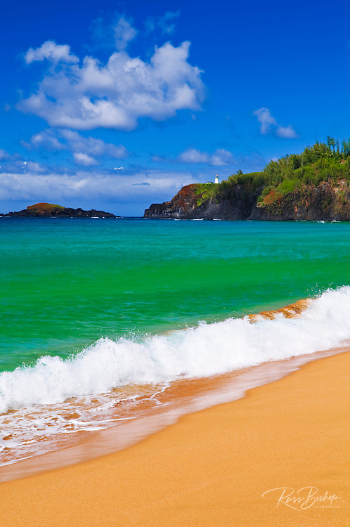 Surf, sand and blue green waters at Secret Beach (Kauapea Beach), Kilauea Lighthouse visible, Island of Kauai, Hawaii