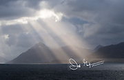 Rays of sunlight beam through dark clouds onto the Beagle Channel, Tierra del Fuego, southern tip of South America.