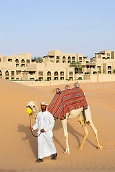 Arab man with camel at Qasr al Sarab Hotel by Anantara in Empty Quarter of Abu Dhabi United Arab Emirates