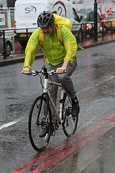 © Licensed to London News Pictures. 17/11/2015. London, UK. A cyclist rides through surface water on London Bridge in London during wet and windy weather today. Photo credit : Vickie Flores/LNP