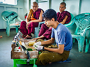 20 NOVEMBER 2017 - YANGON, MYANMAR: A betel vendor prepares an order for monks on the Dala Ferry. Tens of thousands of commuters ride the ferry every day. It brings workers into Yangon from Dala, a working class community across the river from Yangon. A bridge is being built across the river, downstream from the ferry to make it easier for commuters to get into the city.     PHOTO BY JACK KURTZ