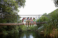Four teenagers (16-17 years) backpacking in forest reading map on bridge
