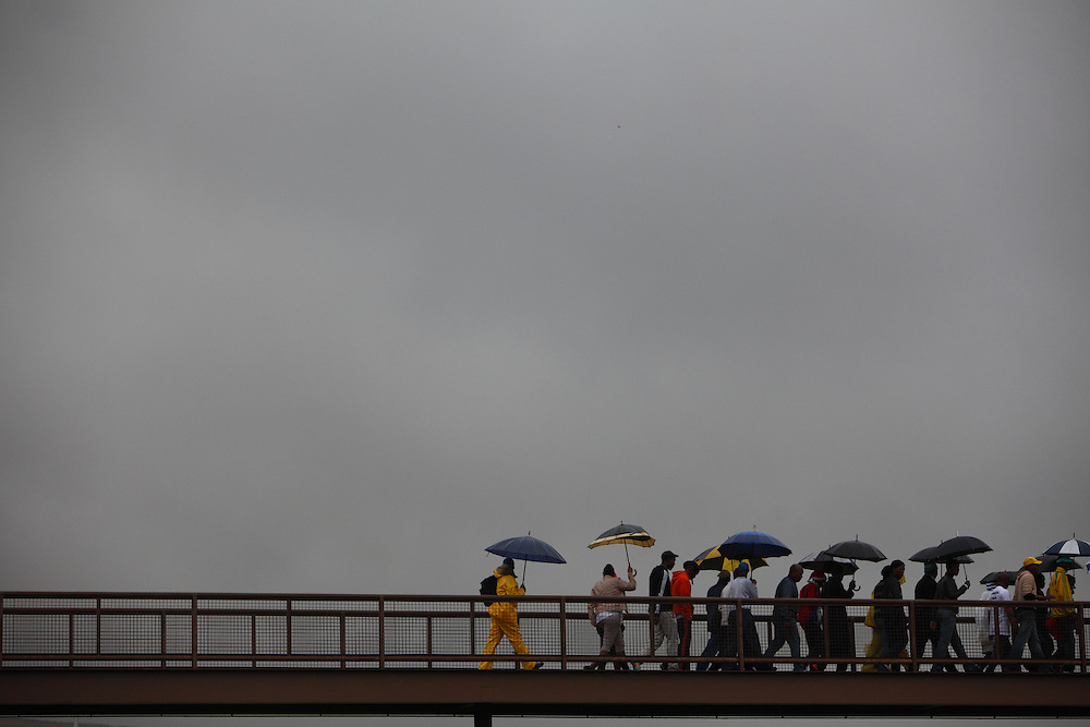 Heading home after a very rainy day at the official memorial service for Nelson Rolihlahla Mandela the FNB stadium in Soweto near Johannesburg. South Africa.<br /> <br /> Tuesday 10th December 2013<br /> Picture by Zute Lightfoot