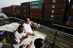 "A group of men watch a cargo ship float through the the Miraflores Lock of the Panama Canal while eating at the Miraflores Restaurant at the Miraflores Visitor Center  l.  Panama is poised to become the ""next Costa Rica"", though tourists have yet to begin flocking to the central american country.  The Capital, Panama City, is home to the Panama Canal and, due to the former US military presence, is one of the continents capitals most comfortable for people from the United States.  The country offers a variety of eco-tourism opportunities as well as a capital that mixes a modern feel with a colonial center."