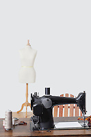 Tailor's dummy and sewing machine with threads over gray background