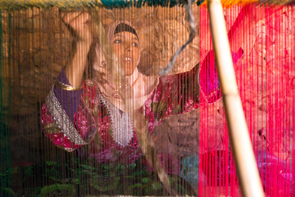 TALIOUINE, MOROCCO - MAY 25TH 2016 - Portrait of Amazigh women weaving a carpet using a traditional loom, Taliouine province of the Souss Massa Draa, Southern Morocco.