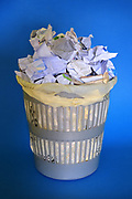A basket full of paper on blue background.