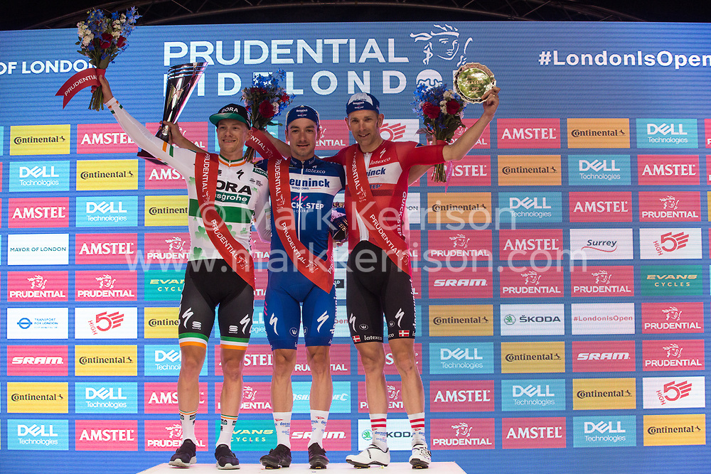 London, UK. 4 August, 2019. Elia Viviani of Deceuninck-Quick-Step stands on the podium with Sam Bennett of Bora-Hansgrohe (who finished second) and Michael Morkov of Deceuninck-Quick-Step (who finished third) after winning the Prudential RideLondon Classic, Britain's only men's UCI WorldTour race and the richest one-day race in the world with a prize pot of 100,000 Euros on offer. This year's race features a redesigned race route from a start in Bushy Park in south-west London through Surrey, including a five-lap circuit of Box Hill, to a finish on the Mall.