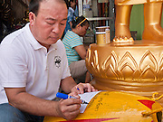 "05 JULY 2011 - BANGKOK, THAILAND:    A man writes an inscription on a Buddhist bell meant for a special occasion before selling it to some monks in his store on Bamrung Muang Street in Bangkok. Thanon Bamrung Muang (Thanon is Thai for Road or Street) is Bangkok's ""Street of Many Buddhas."" Like many ancient cities, Bangkok was once a city of artisan's neighborhoods and Bamrung Muang Road, near Bangkok's present day city hall, was once the street where all the country's Buddha statues were made. Now they made in factories on the edge of Bangkok, but Bamrung Muang Road is still where the statues are sold. Once an elephant trail, it was one of the first streets paved in Bangkok, it is the largest center of Buddhist supplies in Thailand. Not just statues but also monk's robes, candles, alms bowls, and pre-configured alms baskets are for sale along both sides of the street.         PHOTO BY JACK KURTZ"