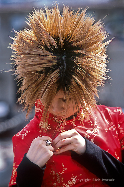 A youth with spiky hair adjusts her red shirt in the Harajuku district, Tokyo, Japan