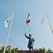 A bronze statue of Miguel Hidalgo with flags raised proudly, stands in Hidalgo Square.  The small park is found at the end of Puerto Vallarta's Hotel Zone, one block away from the boardwalk (Malecón). Photo by William Drumm.