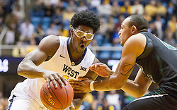 Nov 20, 2015; Morgantown, WV, USA; West Virginia Mountaineers forward Devin Williams drives to the basket past Stetson Hatters forward Derick Newton during the first half at WVU Coliseum. Mandatory Credit: Ben Queen-USA TODAY Sports