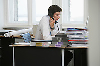 Business man using telephone at desk in office